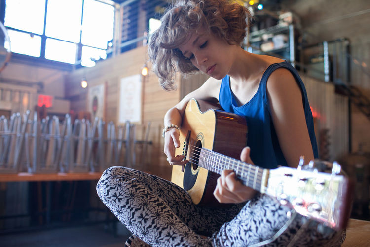 Young woman playing an acoustic guitar