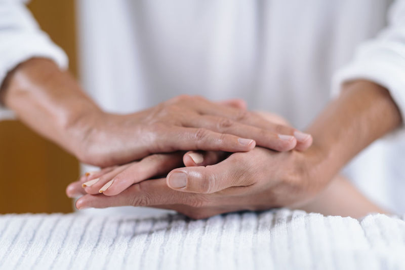 Cropped hands giving massage to women