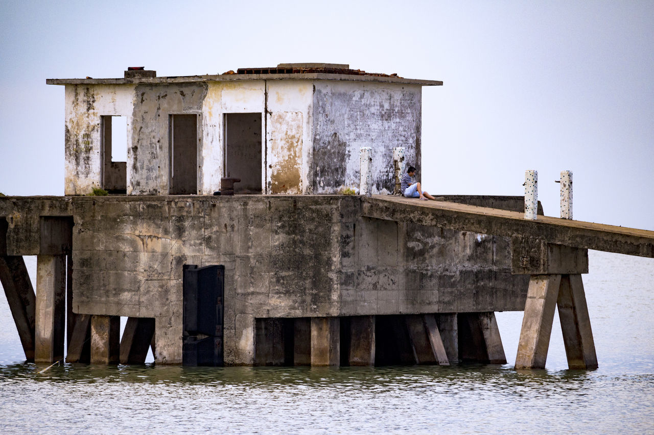 built structure, architecture, water, sky, clear sky, nature, day, damaged, old, abandoned, waterfront, obsolete, sea, run-down, outdoors, decline, weathered, deterioration, no people, ruined