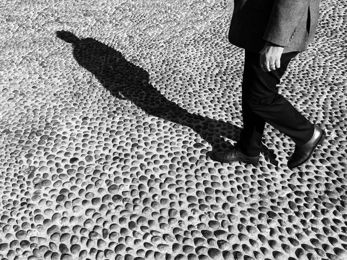Low section of man walking on cobbled street