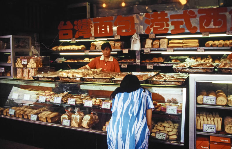 A pastry shop in Guangzhou, Canton, China Guangzhou, Canton, China A Taste Of China Bakers Bakery Buying Casual Clothing Chinese Writing Choice Consumerism Customer  Display Cabinet Food Food And Drink For Sale Freshness Indoors  Indulgence Men Pastry Shop Real People Rear View Retail  Retail Display Shelf Small Business Standing Store Sweet Food Variation Women Food Stories Business Stories Modern Workplace Culture