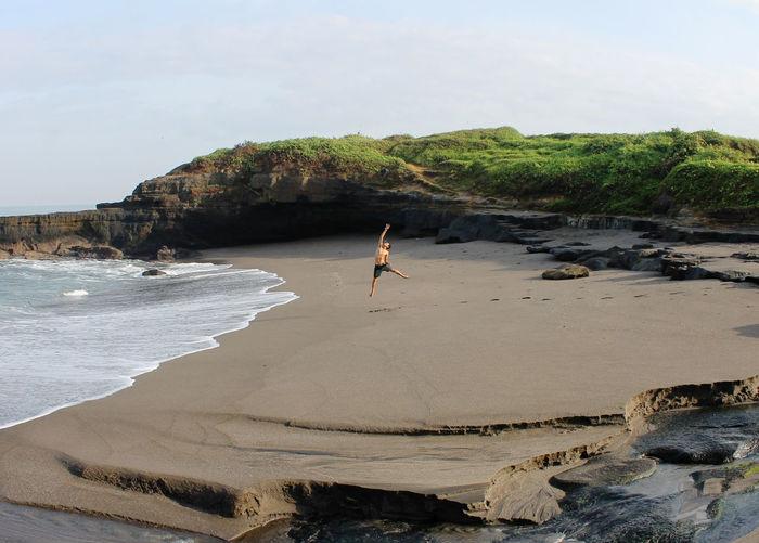 Full length of man jumping at beach against sky