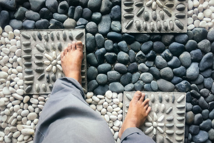 Low section of man standing on pebbles