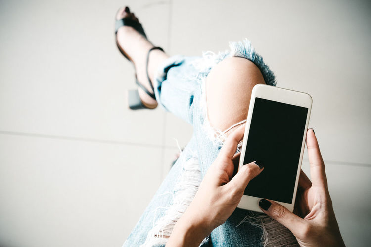 Low section of woman using mobile phone