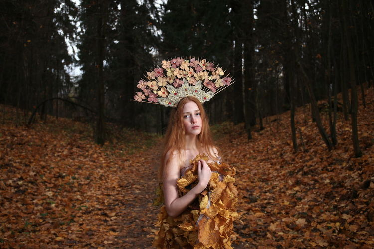 Portrait of young woman wearing flowers on hair standing at forest during autumn