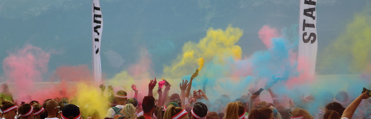 People throwing powder paint while enjoying event in city