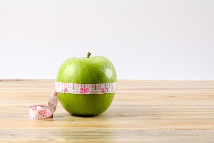 DIET & FITNESS. A GREEN APPLE WITH MEASURING TAPE BMI Diet & Fitness Measuring Tape Challenge Close-up Conceptual Photography  Dieting Food Food And Drink Freshness Fruit Green Apple Healthy Eating Indoors  No People Slimming Still Life Table Wellbeing Wood - Material