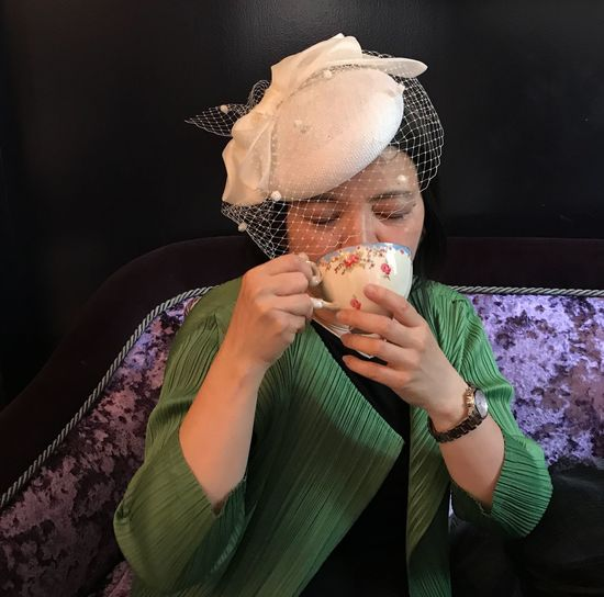 Woman Drinking Coffee While Sitting On Sofa At Home