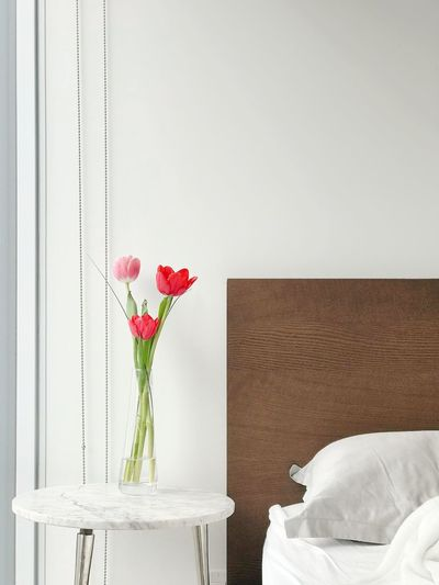 Rose flower vase on table against wall at home
