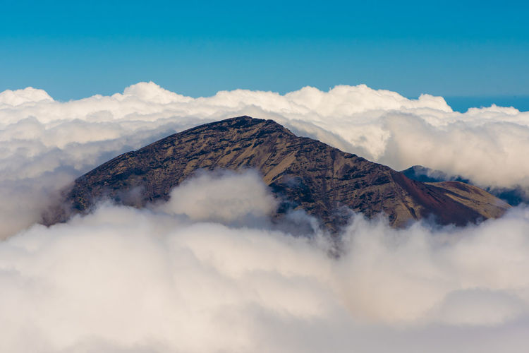 Scenic View Of Mountain Amidst Cloudscape Against Sky