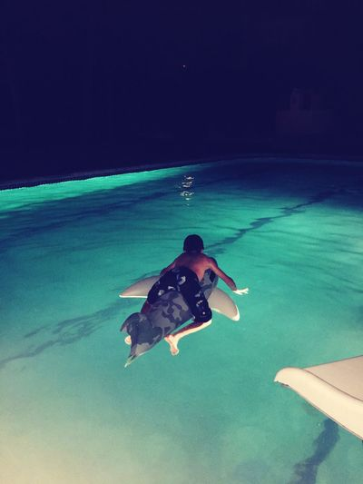 Rear view of shirtless boy surfboarding on swimming pool at night