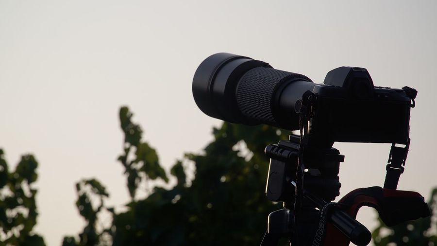 Close-up of home video camera against clear sky