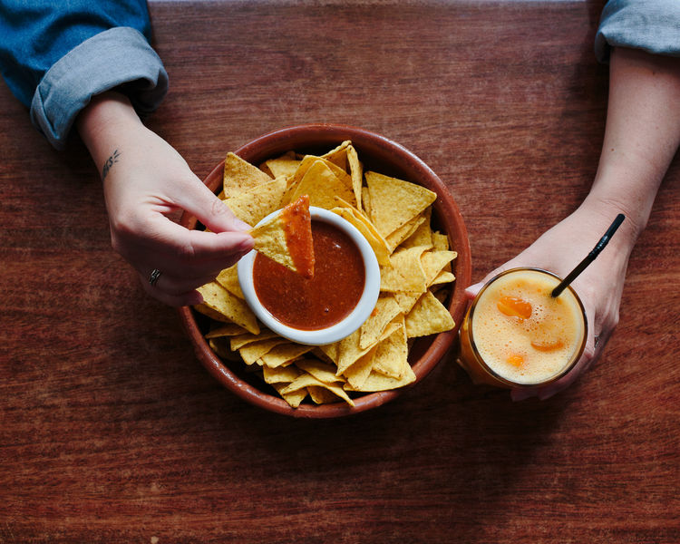 not healthy eating Eating Nachos Bowl Close-up Day Food Food And Drink Freshness Healthy Eating Holding Human Body Part Human Hand Indoors  Lifestyles One Person People Ready-to-eat Real People Table Unhealthy Eating
