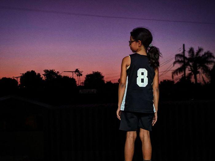 Full length of woman standing against sky during sunset