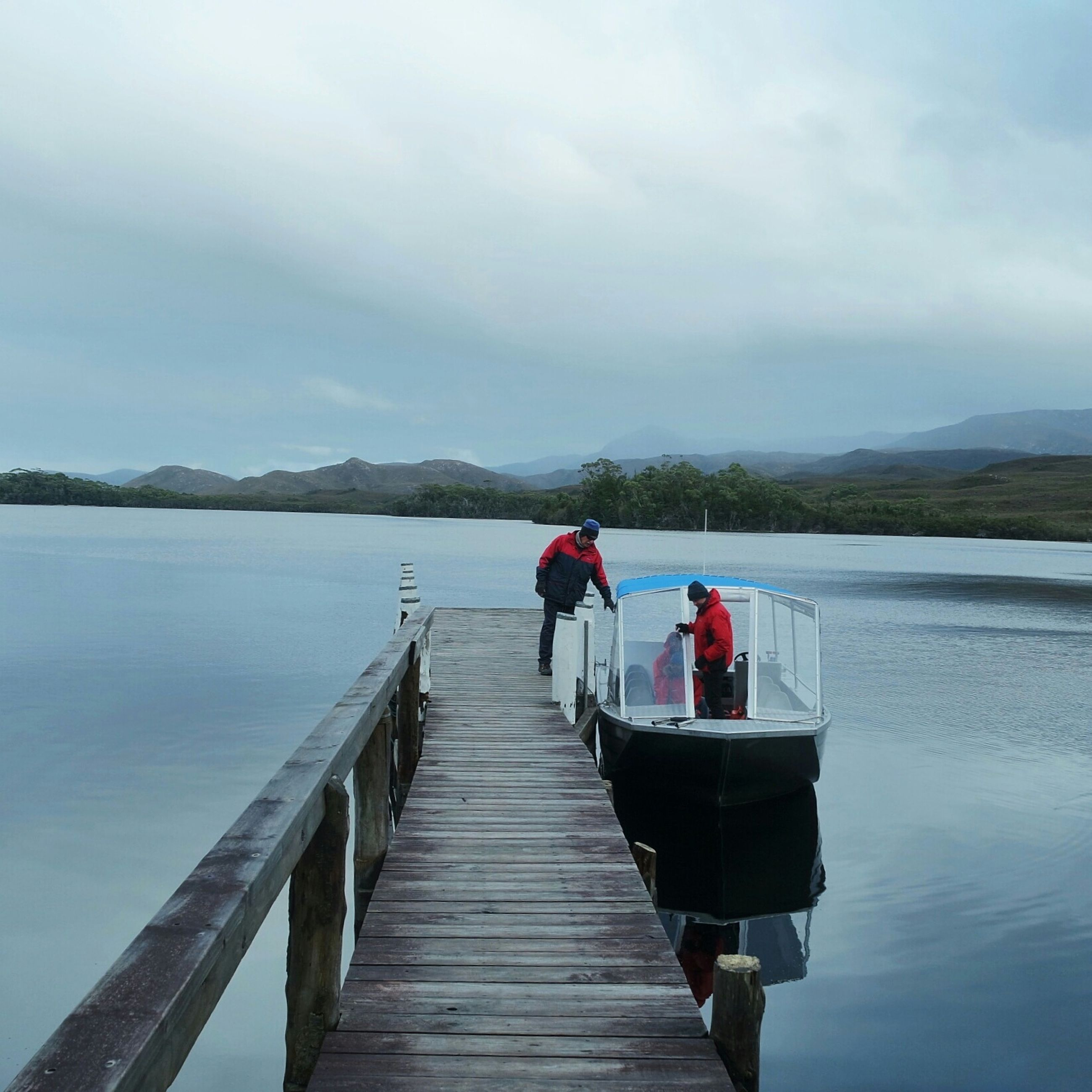 water, mountain, sky, tranquil scene, pier, the way forward, tranquility, lake, scenics, beauty in nature, rear view, nature, mountain range, jetty, railing, cloud - sky, men, boardwalk, leisure activity
