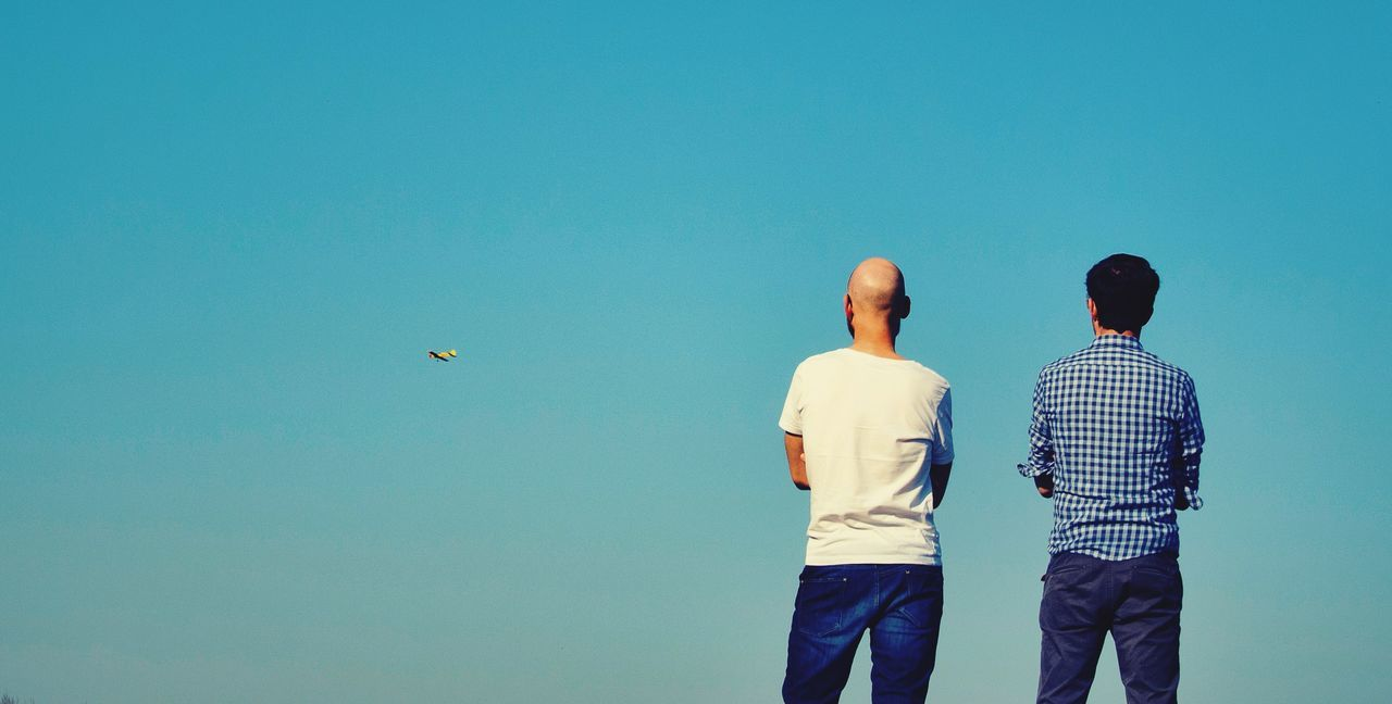 two people, rear view, real people, flying, clear sky, copy space, togetherness, men, day, leisure activity, mid-air, sky, lifestyles, blue, outdoors, bird, adult, people