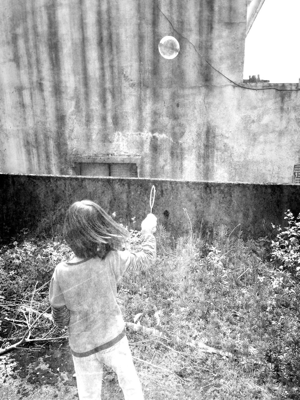 Rear View Of Girl Making Bubble With Wand Against House