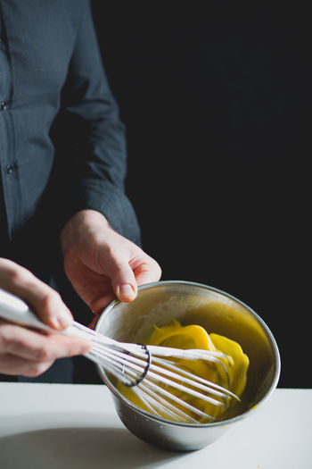 CLOSE-UP VIEW OF CHEF WHISKING EGG
