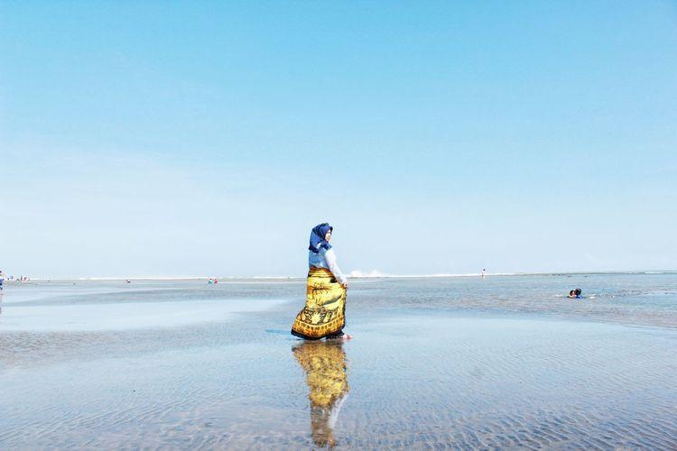 Woman walking at beach against clear blue sky