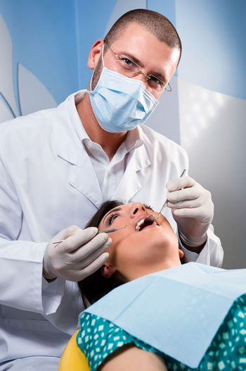 Portrait of male dentist operating female patient in clinic
