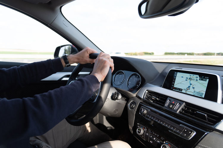 Man driving a luxury car. Interior view Mode Of Transportation Transportation Car Vehicle Interior Steering Wheel Land Vehicle Driving Motor Vehicle Car Interior Hand Human Hand One Person Real People Windshield Control Panel Human Body Part Driving Safety Luxury GPS Navigator  Trip Journey Road Highway Day Dashboard Men Finger