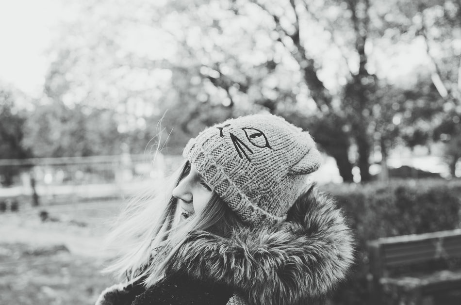 Smiling girl in winter clothing with a nature in the background Autumn Bright Growth Happiness Nature Squinting Sunny Trees Winter Woman Beautiful Woman Beauty Black And White Close-up Focus On Foreground Headshot Knit Hat Over Exposed Park Portrait Scarf Side View Smiling Warm Clothing Young Woman