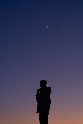Silhouette man standing against moon at night