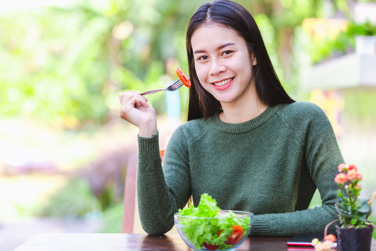 Portrait of smiling woman holding food on table