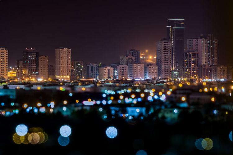 Defocused image of illuminated lights against buildings at night