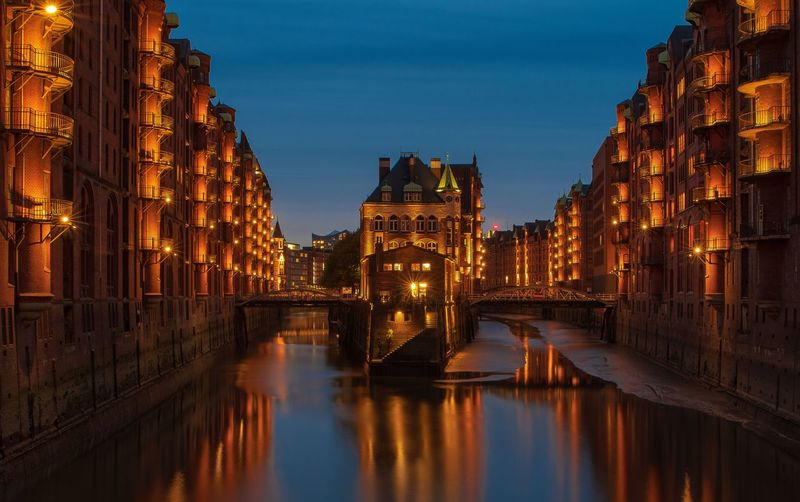 Canal amidst illuminated city buildings against sky at night