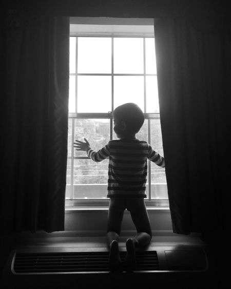 Boy kneeling in front of window