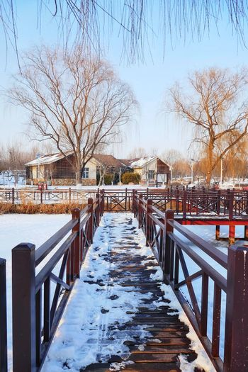 Snow covered footbridge over frozen canal against sky