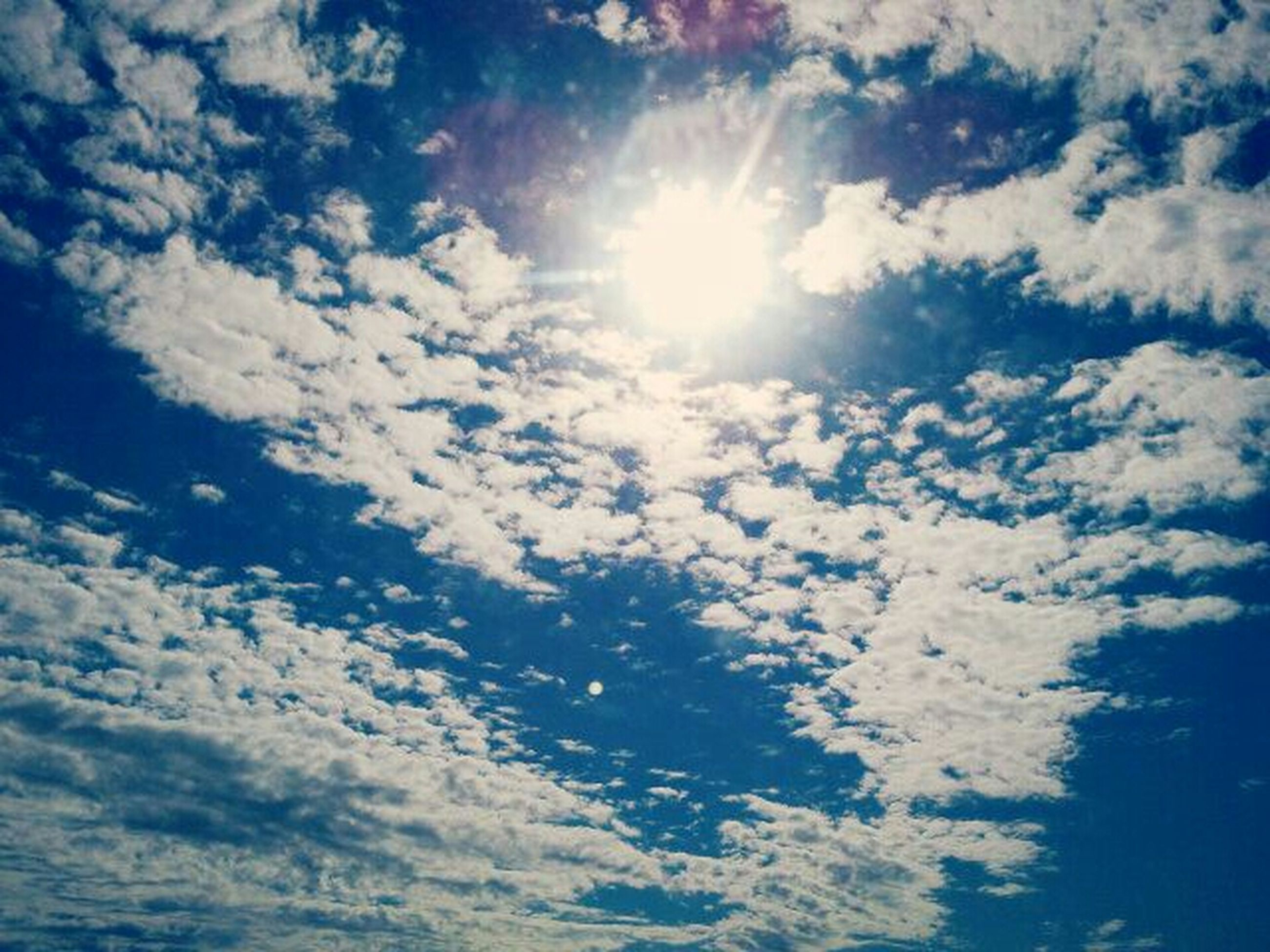 sky, low angle view, sun, cloud - sky, beauty in nature, sunbeam, tranquility, sunlight, scenics, sky only, nature, blue, tranquil scene, cloud, cloudscape, cloudy, idyllic, backgrounds, lens flare, sunny