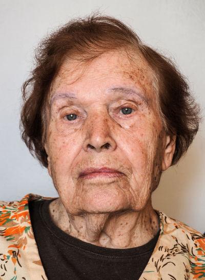Portrait of senior woman against wall