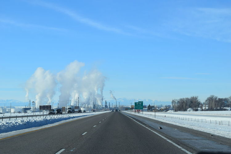 Road By Factory Emitting Smoke Against Blue Sky