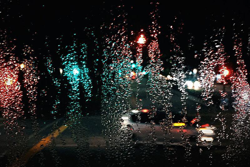 Illuminated city seen through wet glass window
