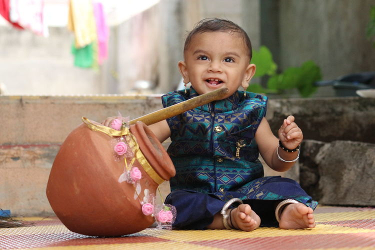 Cute Baby Boy Sitting With Pot And Stick Outdoors