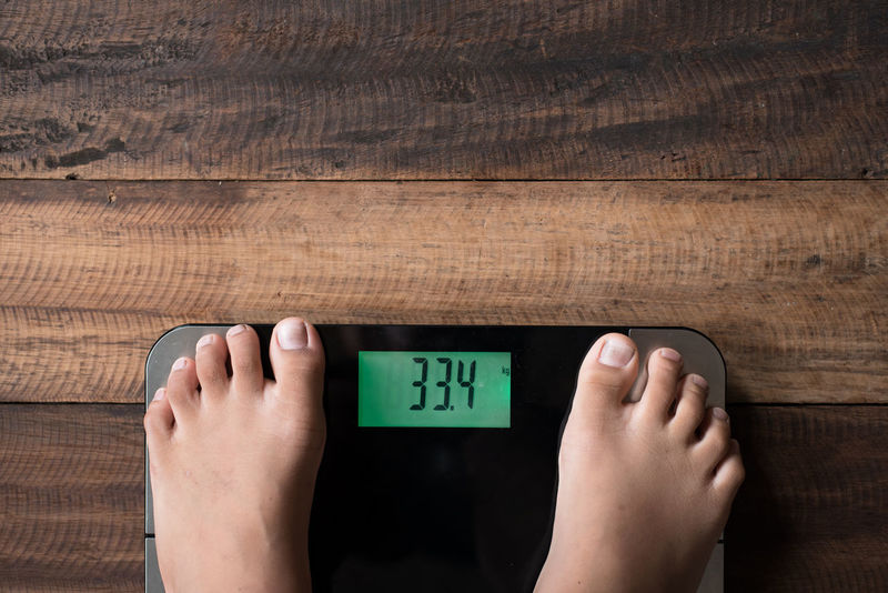 boy measure weight Diet Eating Lifestyle Measuring Standing Weighing Scale Background Boy Control Day Digital Directly Above Fat Feet Health Healthy Indoors  Loose Mass Measure Obsessed One Person Underweight Weight Wooden