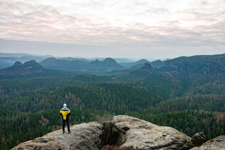 Silhouette of photographer standing on the rocky mountain in rays of sunrise. sudetes