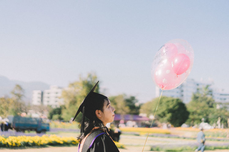 Side view of young woman holding balloon against sky