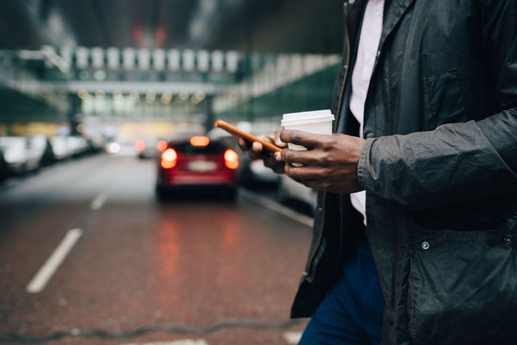 Man holding mobile phone while standing on street in city