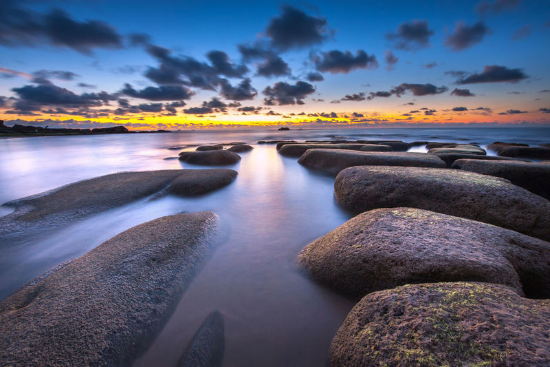 Stones At Seashore Against Cloudy Sky During Sunset