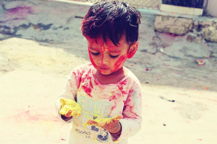 High angle view of baby boy with powder paint while standing outdoors