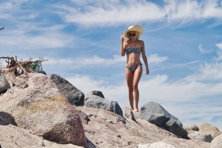 Woman wearing bikini while walking on land against sky