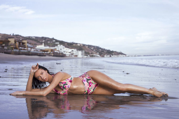 Young woman in bikini lying on shore at beach against sky
