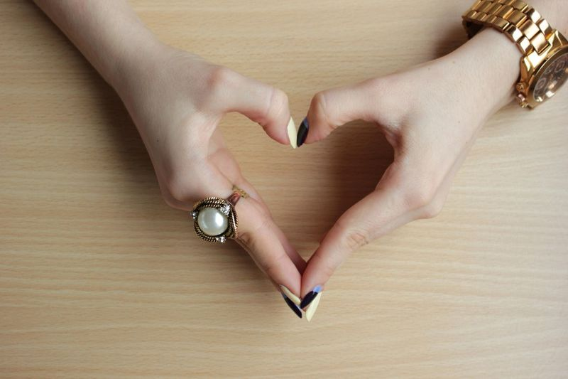 Close-up of hands forming heart shape on wooden table