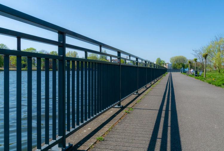 Spree Architecture Blue Built Structure Clear Sky Connection Day Diminishing Perspective Direction Empty Light And Shadow Long Metal Nature No People Oberschöneweide Outdoors Plant Rail Transportation Railing River Sky Sunlight The Way Forward Track Transportation Tree Treptow Water