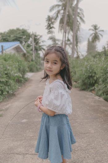 Portrait of smiling girl standing against trees