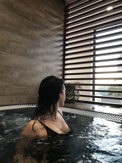Woman in hot tub by window