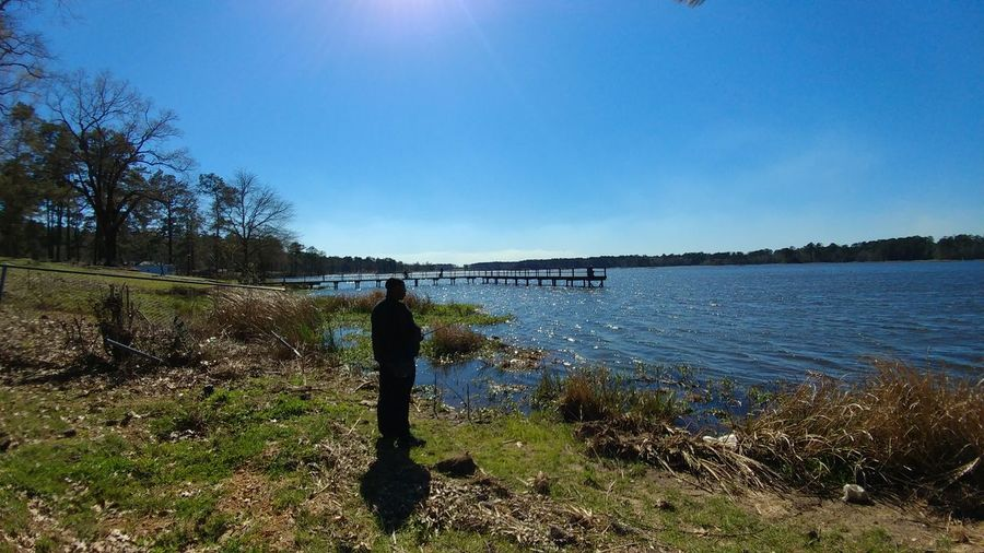 Man standing on riverbank against clear blue sky